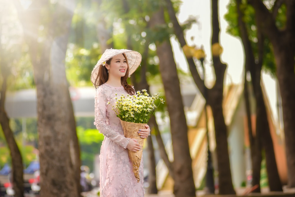 woman in white floral dress holding bouquet of flowers