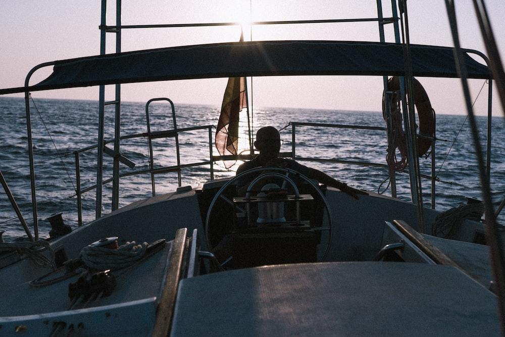 man in black shirt sitting on boat during daytime