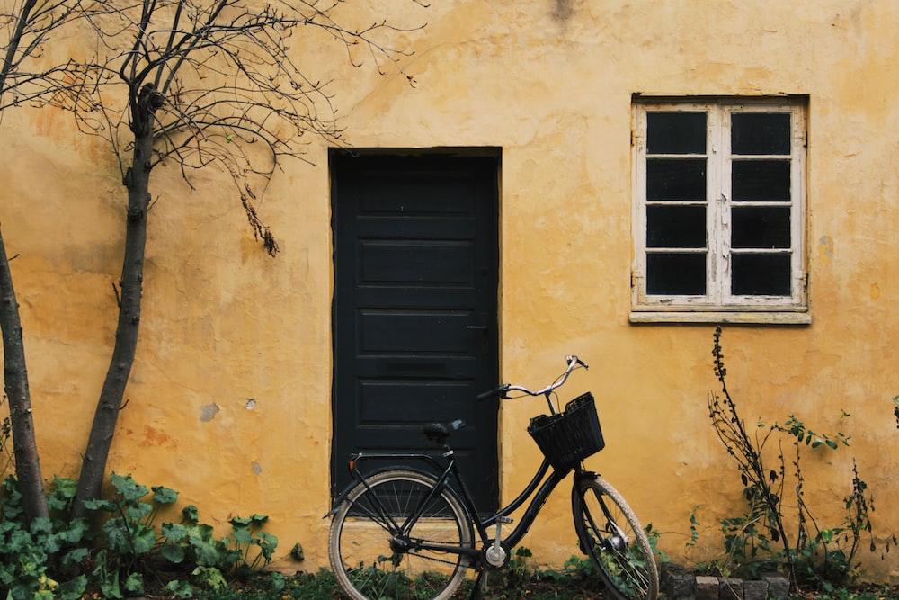 black city bike parked beside black wooden door
