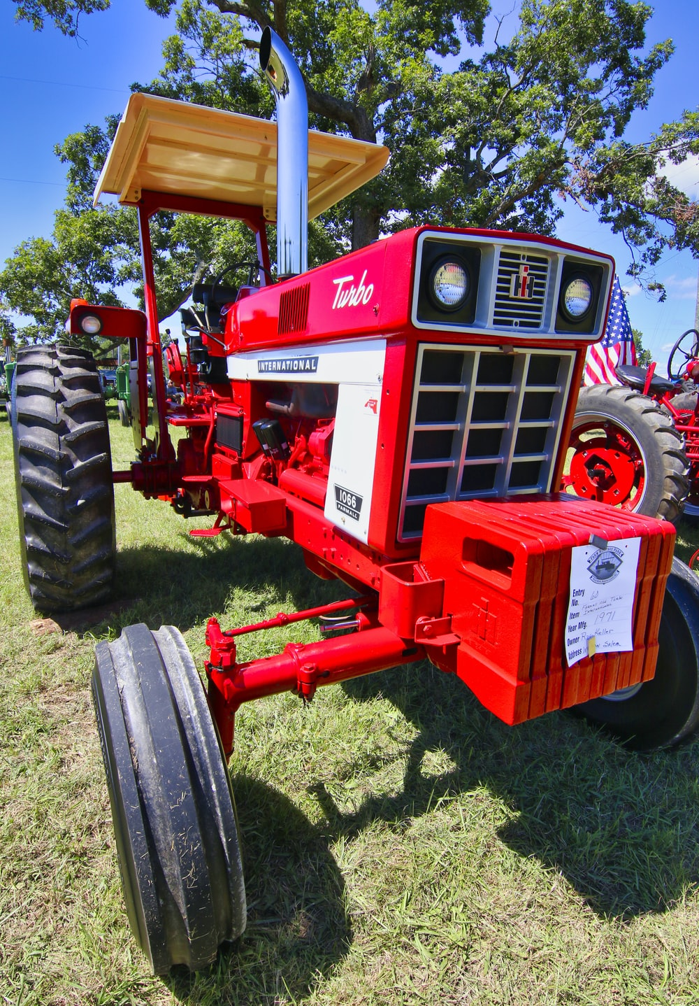 red and black tractor on green grass field during daytime