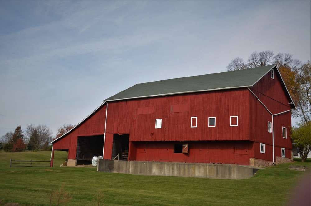 red and black barn house under white clouds