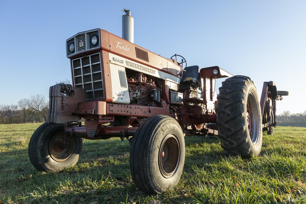 red tractor on green grass field during daytime
