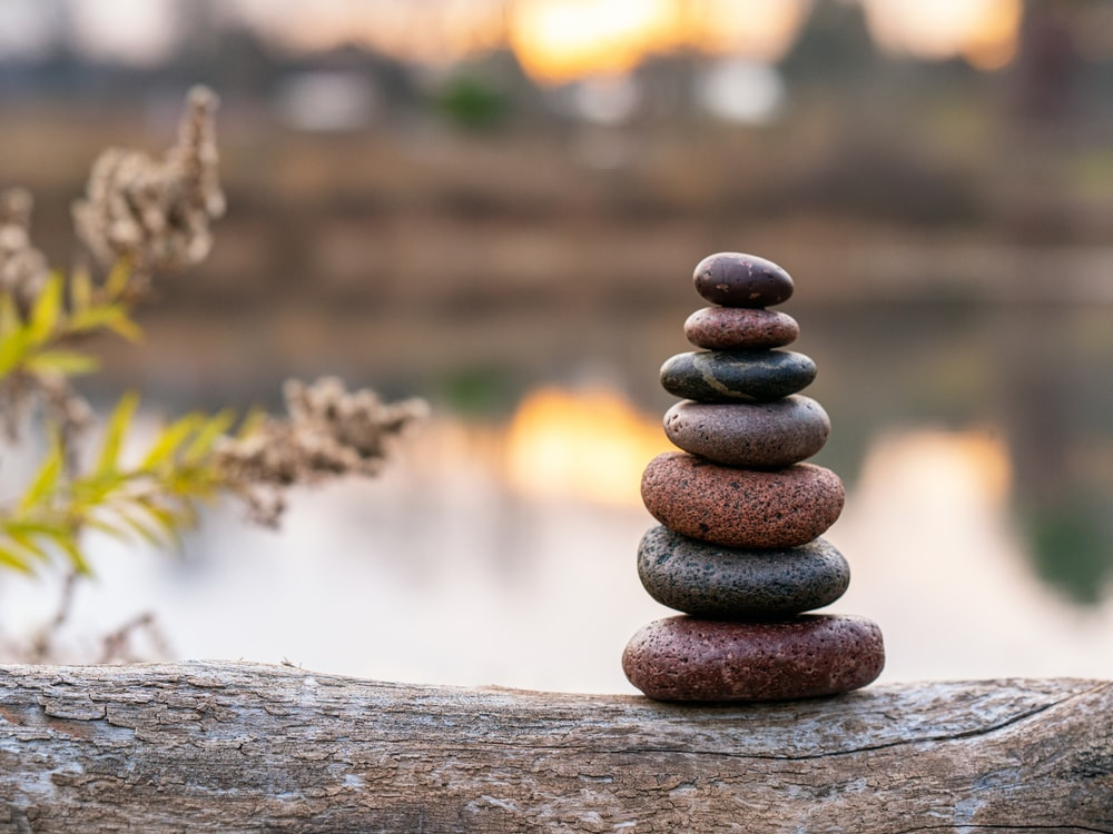 brown stone stack on brown wooden log