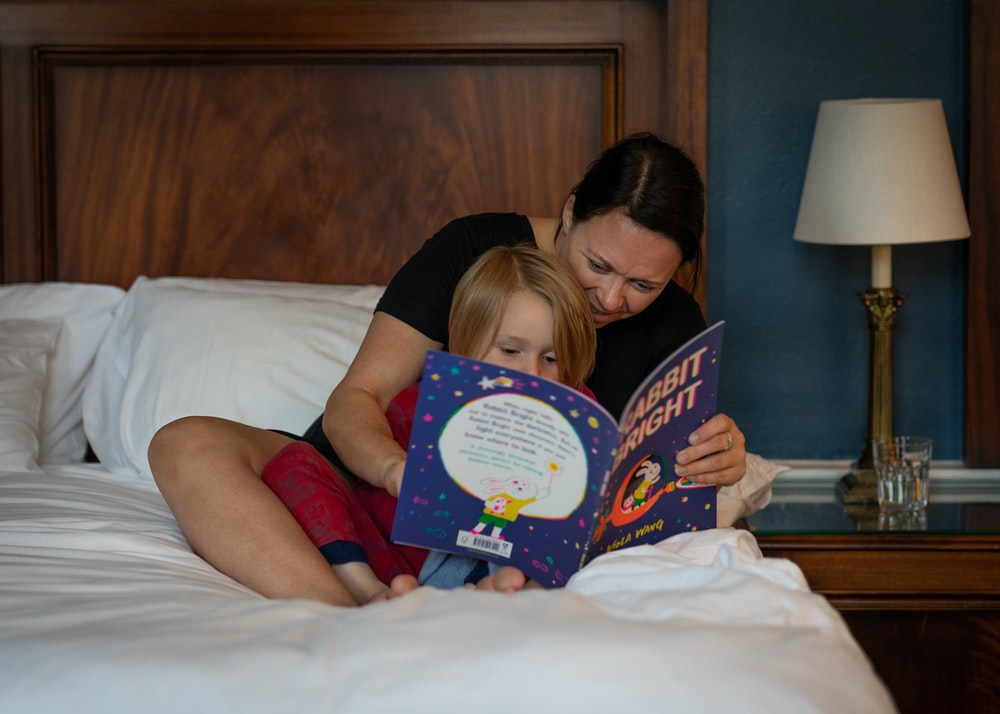 girl in red shirt lying on bed reading book