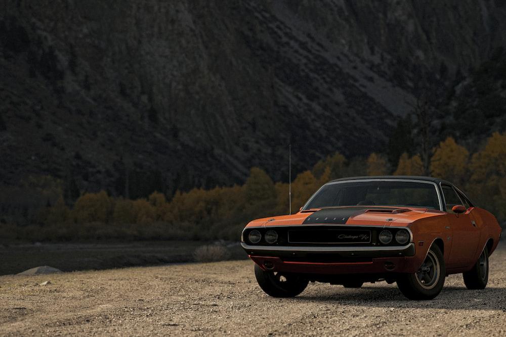orange chevrolet camaro on dirt road during daytime