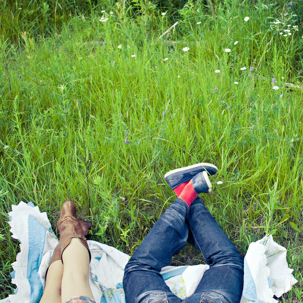 woman in blue denim jeans lying on white textile on green grass field during daytime