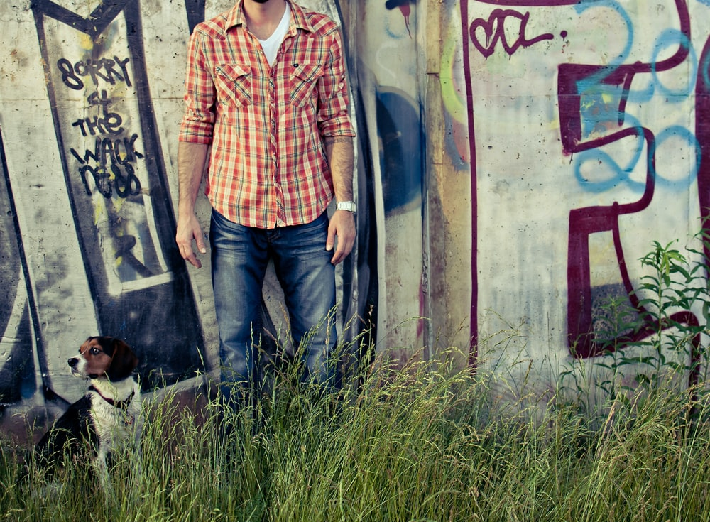 man in orange and white plaid button up shirt standing beside wall with graffiti during daytime