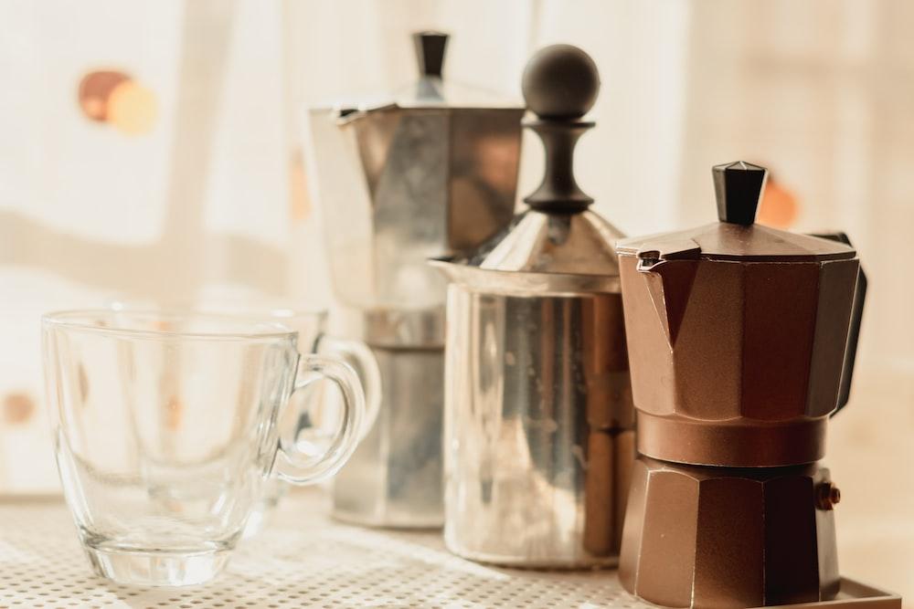 stainless steel teapot beside clear glass mug