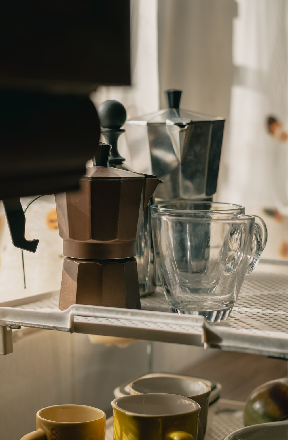 clear drinking glass on stainless steel coffee maker