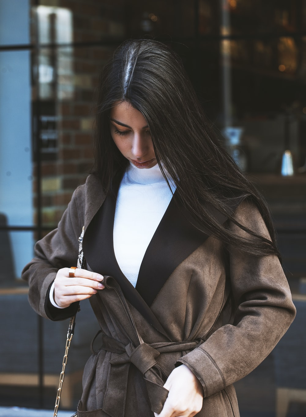 woman in brown coat holding her hair