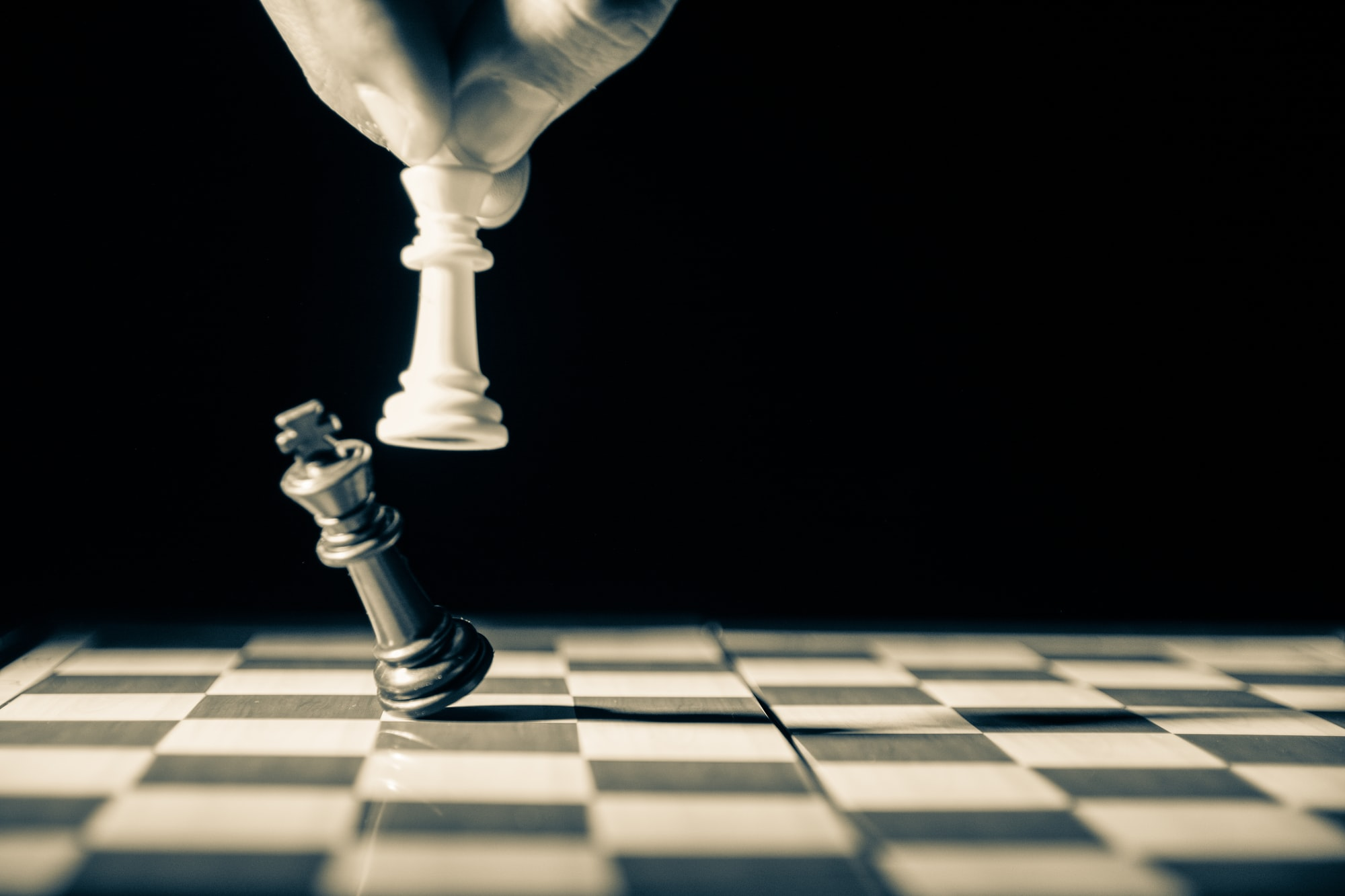 Close up of white king taking down black king. Hand and fingers and chess board with vintage look