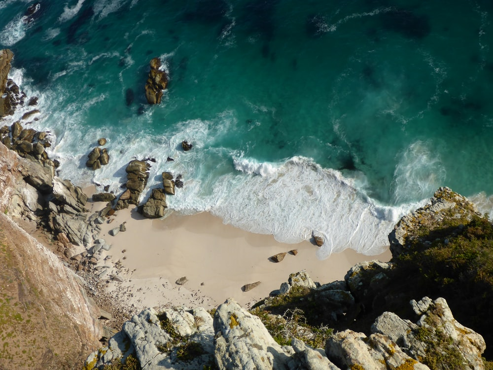 aerial view of sea waves crashing on brown rocky shore during daytime