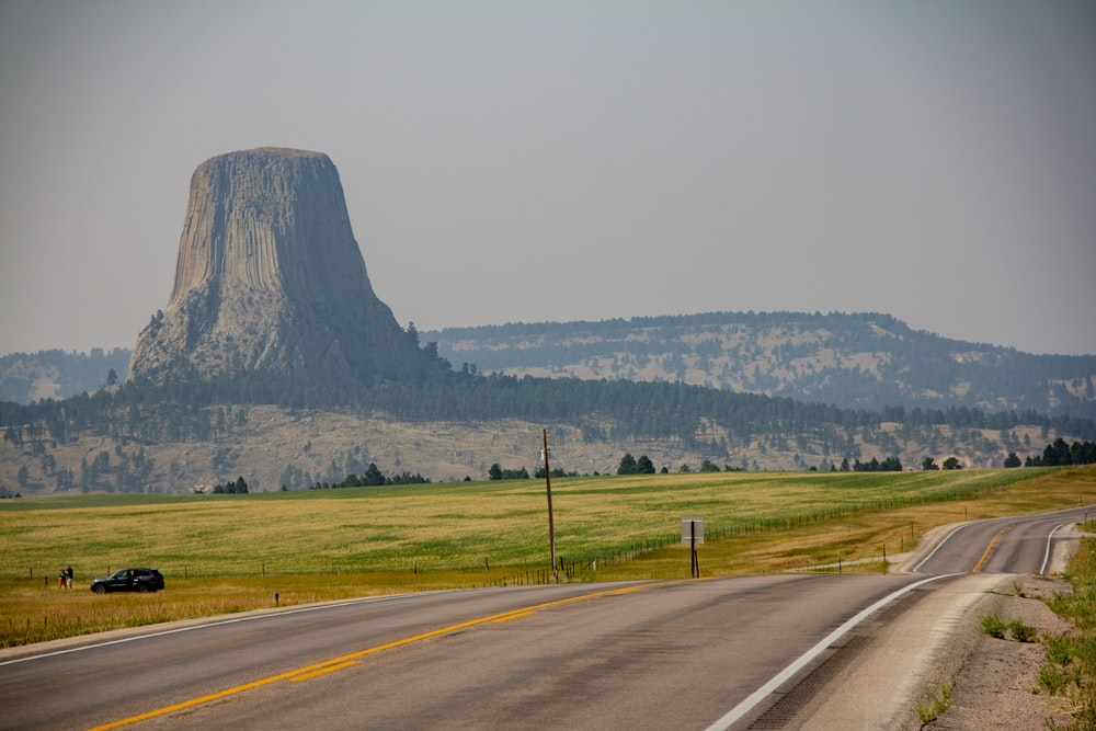 gray asphalt road near green grass field during daytime