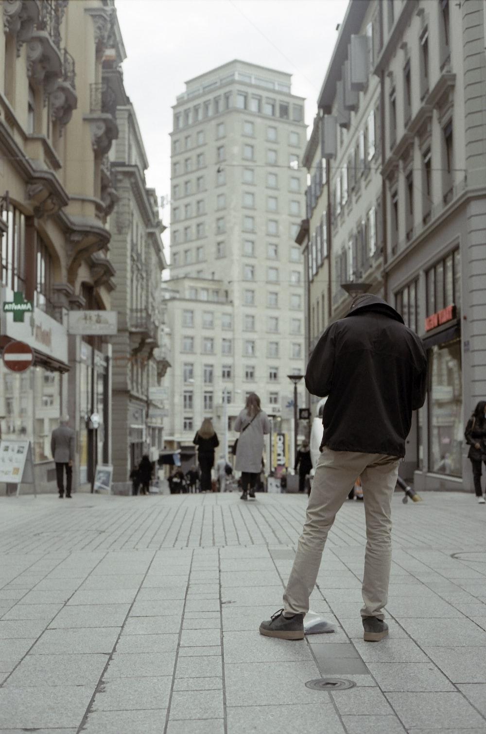 man in black hoodie and gray pants walking on sidewalk during daytime