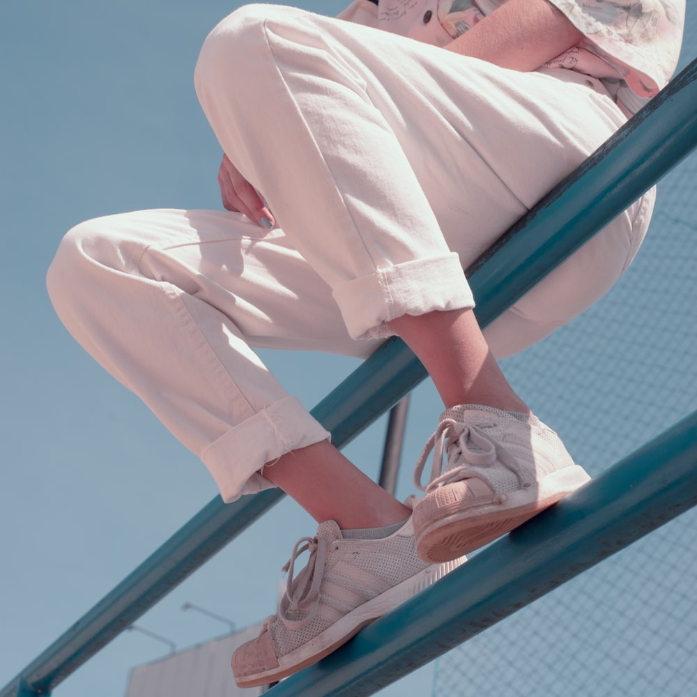person in white pants and white sneakers sitting on blue metal railings