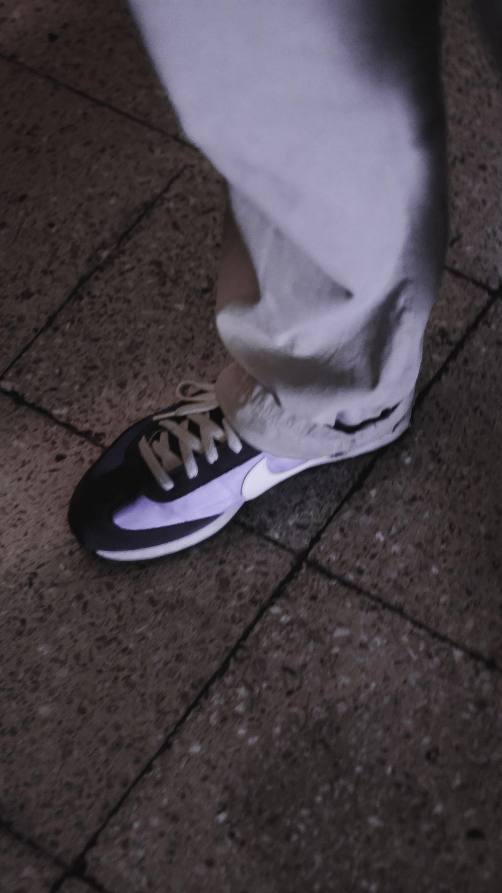 person wearing black and white nike sneakers