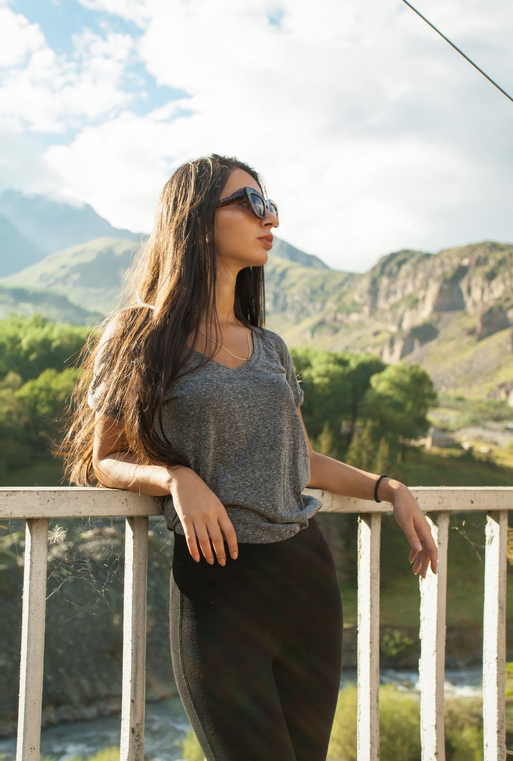 woman in gray crew neck shirt and black pants wearing black sunglasses standing on brown wooden