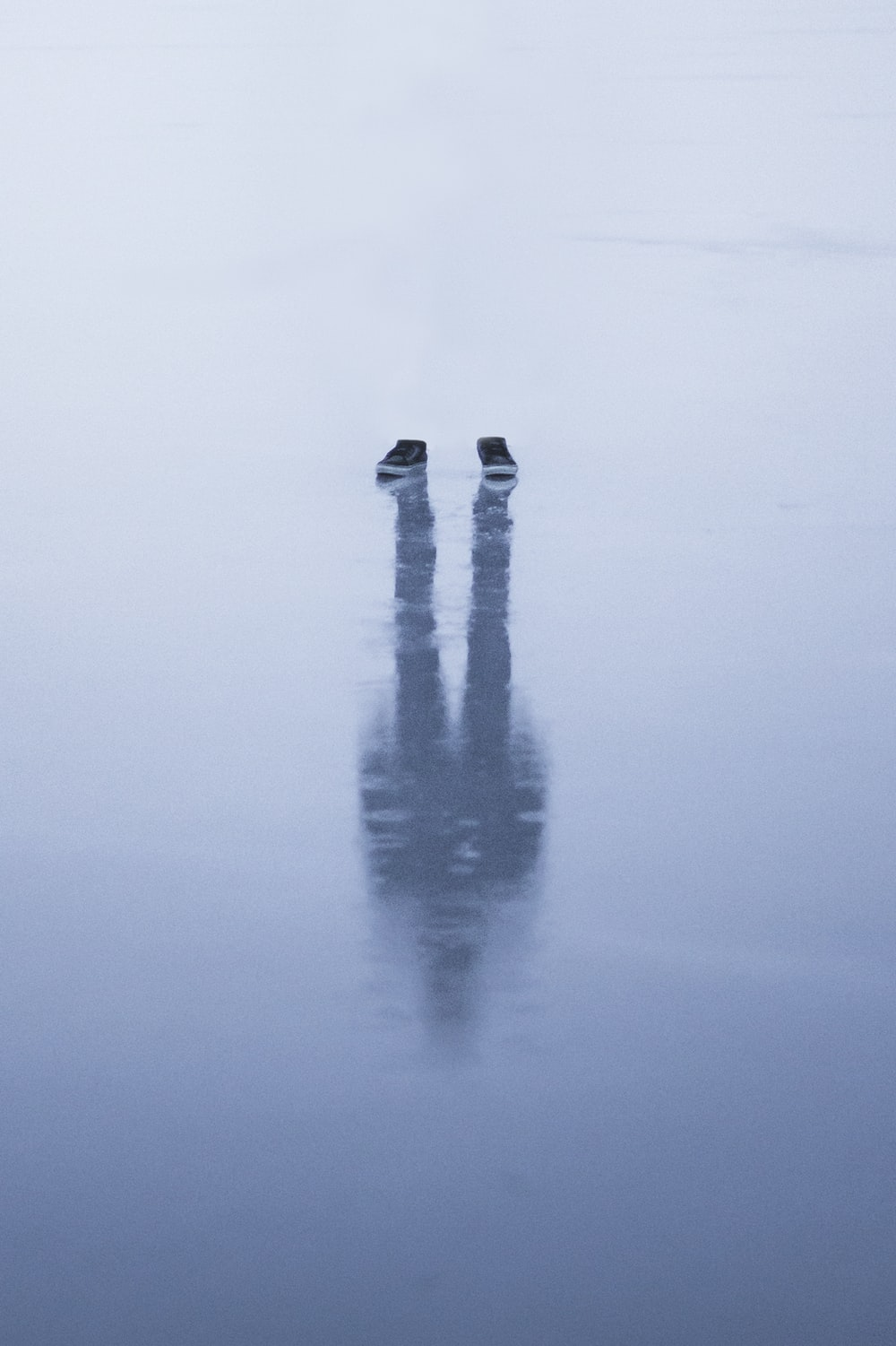 person in black pants standing on water