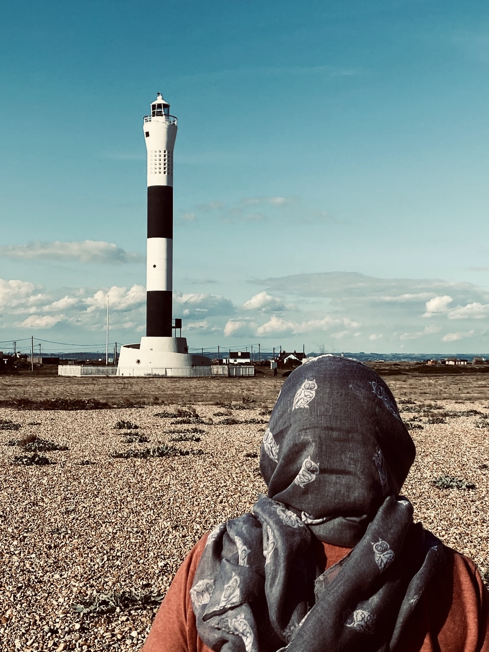 person in gray leather jacket sitting on brown sand near white and red lighthouse during daytime