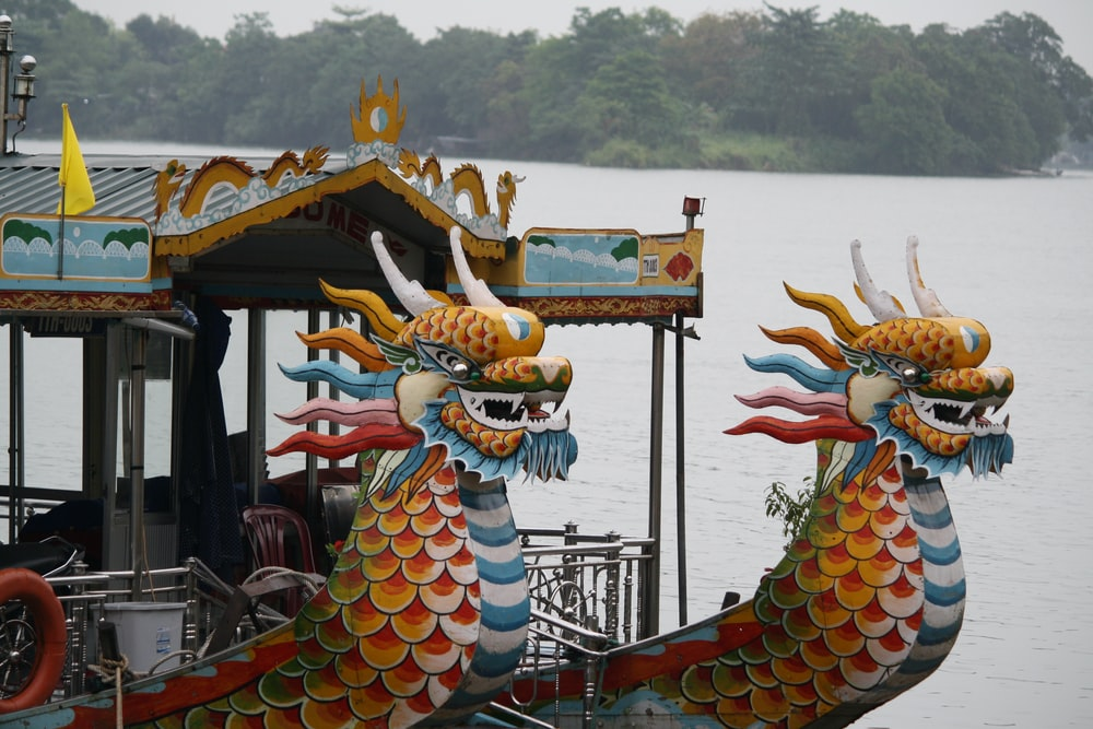 yellow and blue dragon on brown wooden boat