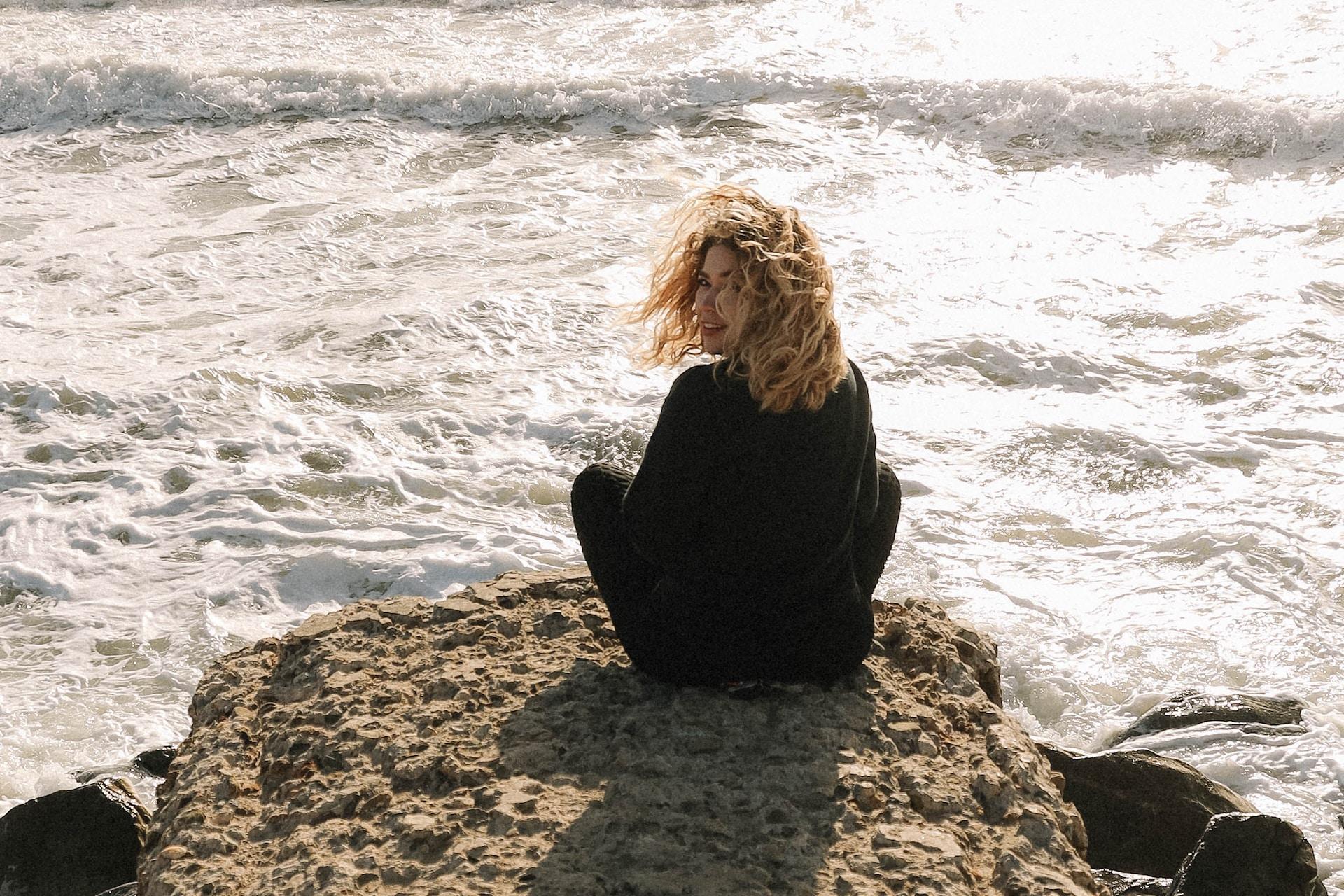 woman in black long sleeve shirt sitting on brown rock near sea during daytime