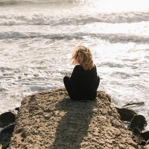 woman in black long sleeve shirt sitting on brown rock near sea during daytime