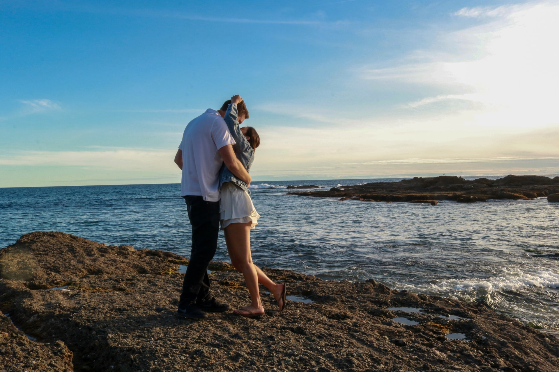 man and woman kissing on seashore during daytime