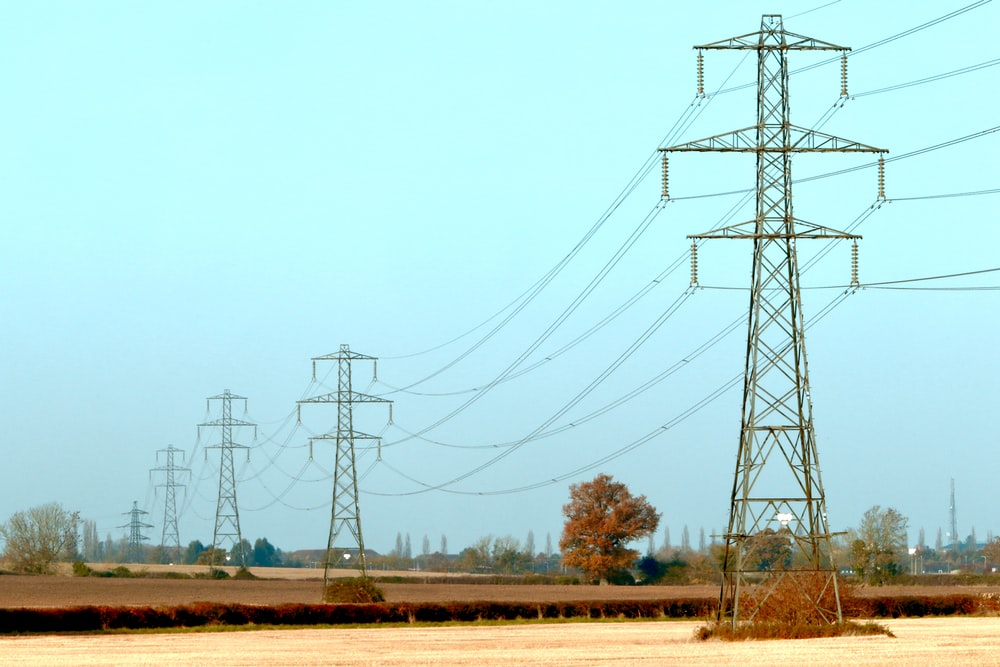 brown and black electric towers under white sky during daytime