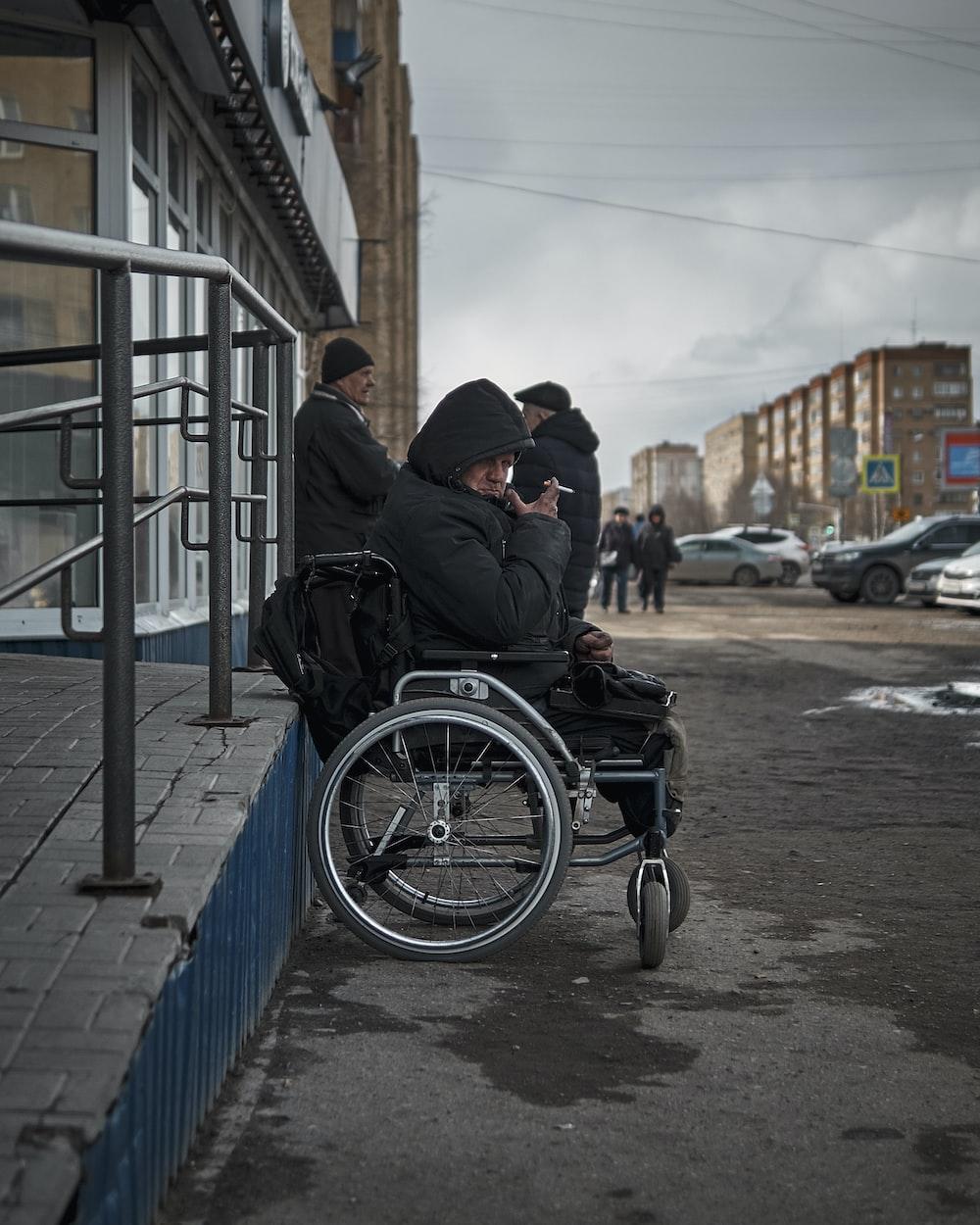 man in black jacket sitting on black wheelchair