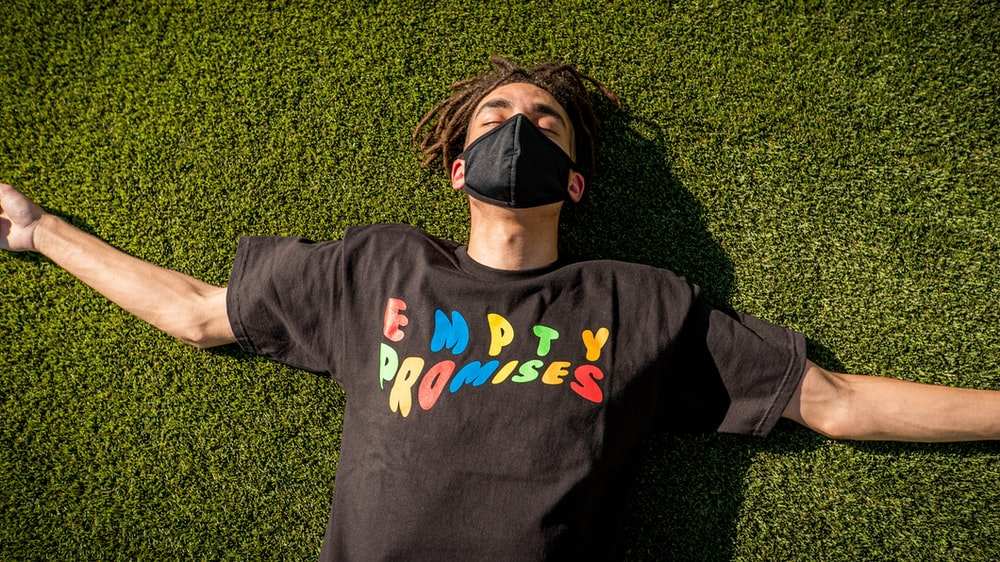 man in black and blue crew neck long sleeve shirt lying on green grass field during