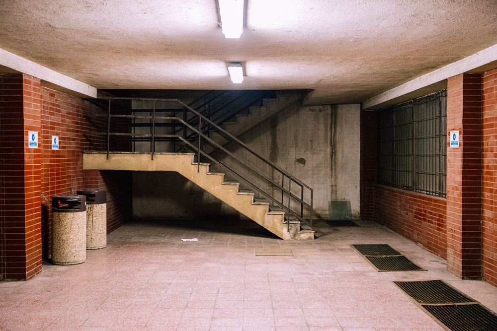 brown concrete staircase with stainless steel railings