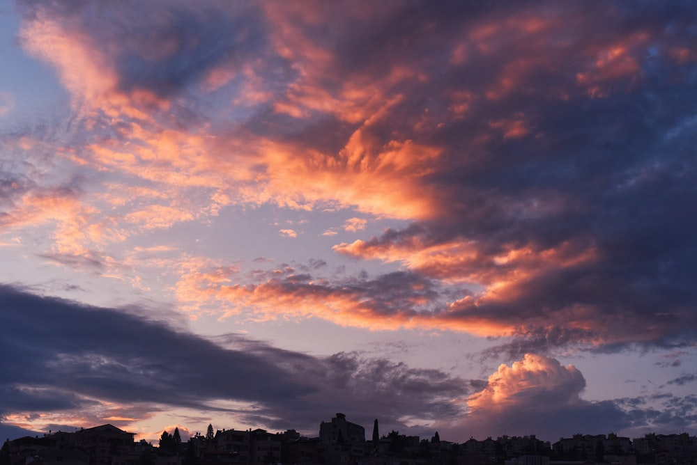 silhouette of buildings under orange and gray clouds