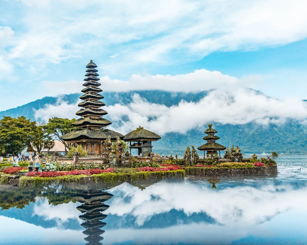 Brown And Green Temple Near Body Of Water Under Blue And White Cloudy Sky During Daytime
