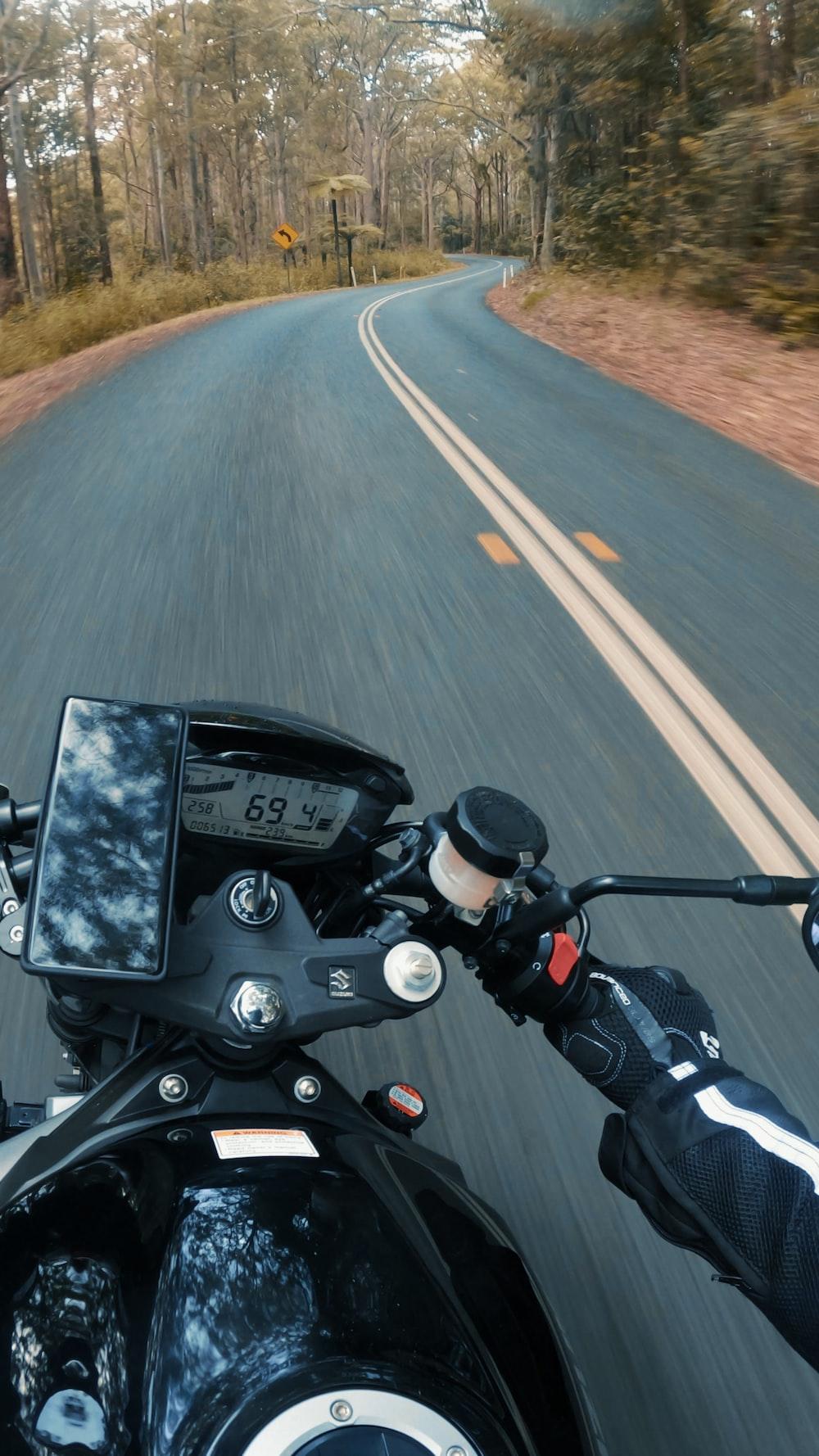 black motorcycle on gray asphalt road during daytime