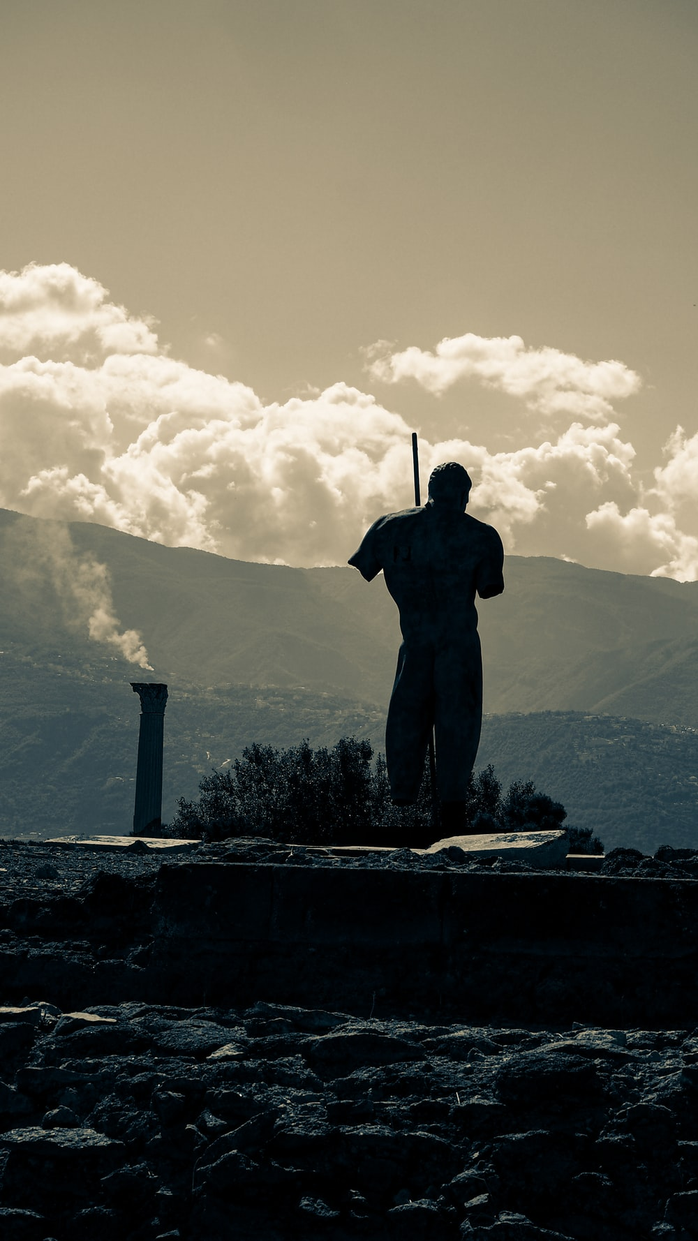 silhouette of man standing on concrete wall near mountain under cloudy sky during daytime