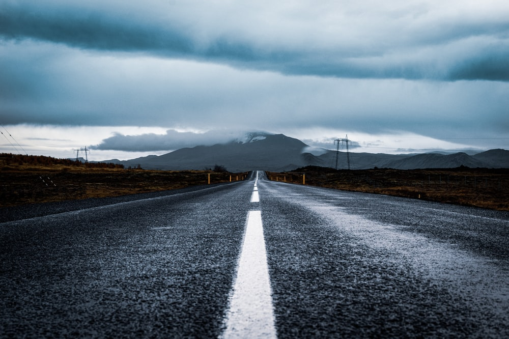 gray asphalt road under gray cloudy sky during daytime