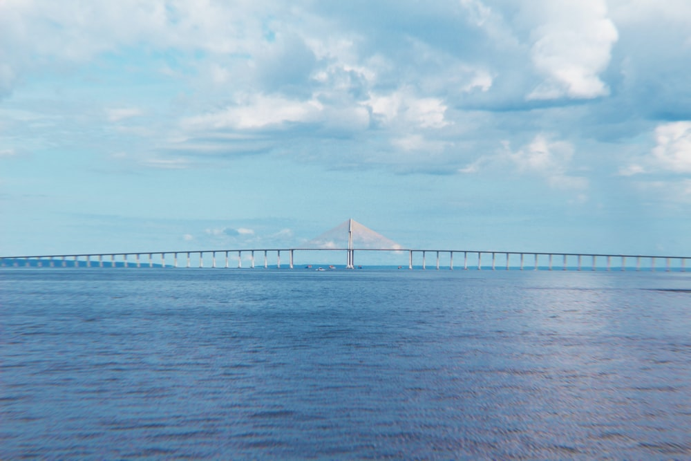 white bridge over the sea under white clouds during daytime