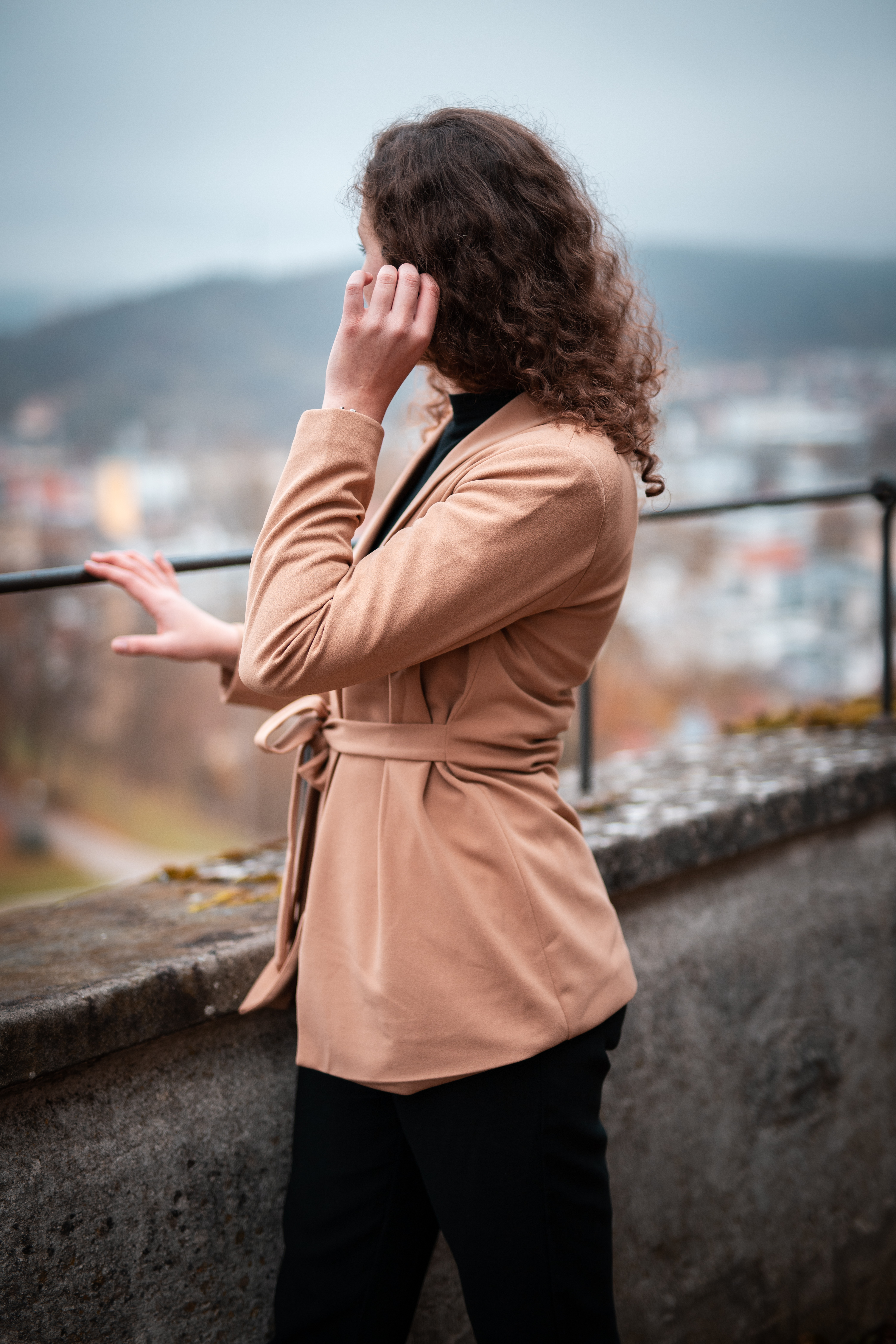 woman-in-brown-coat-standing-on-gray-concrete-wall-during-daytime