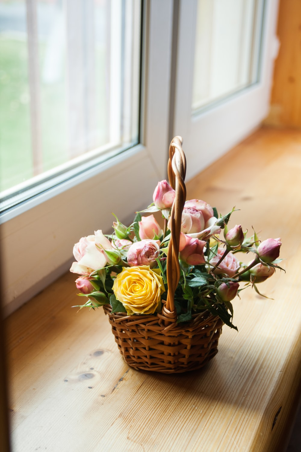 pink and white roses in brown woven basket