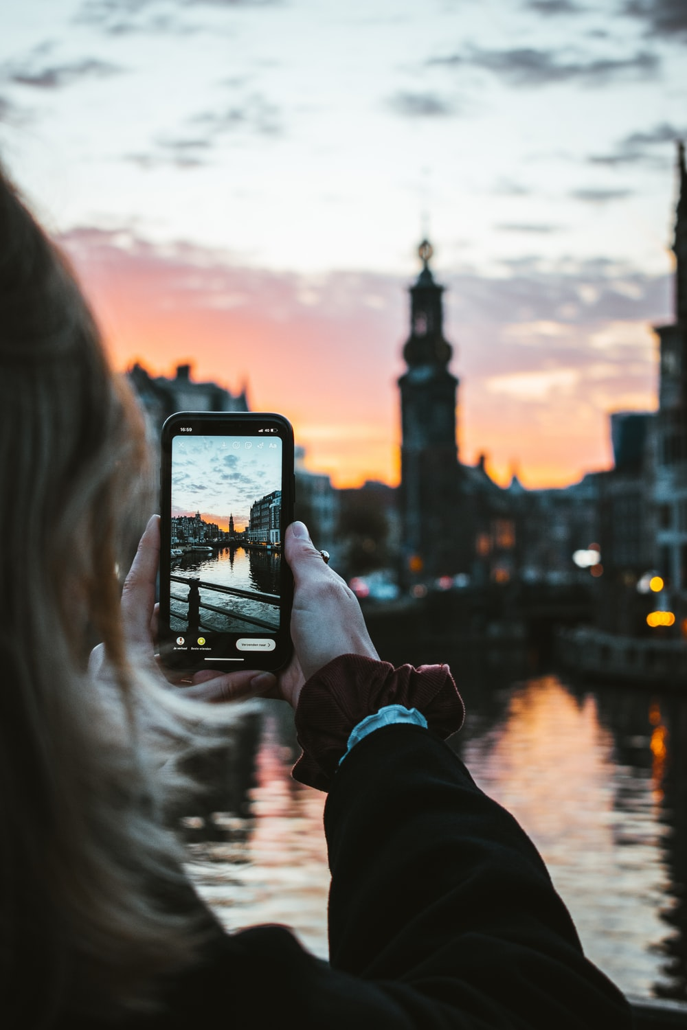 person holding black smartphone taking photo of city buildings during sunset