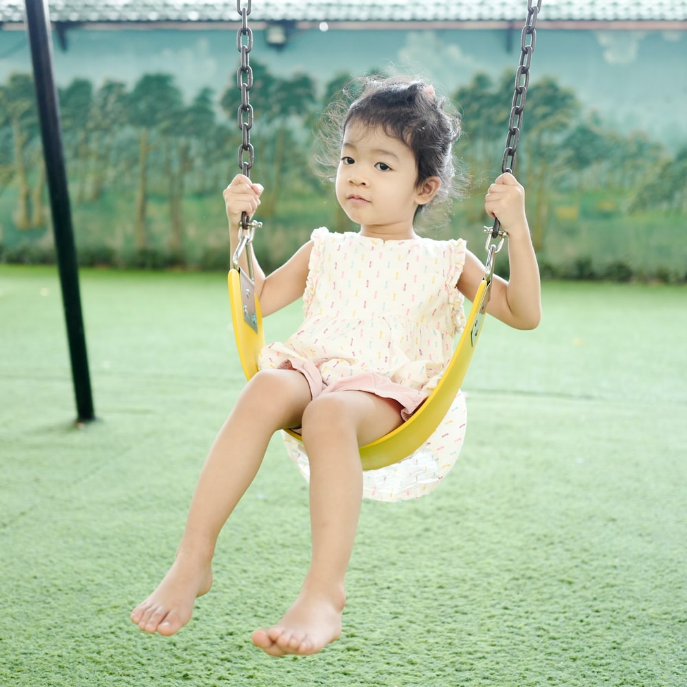girl in pink dress sitting on swing during daytime