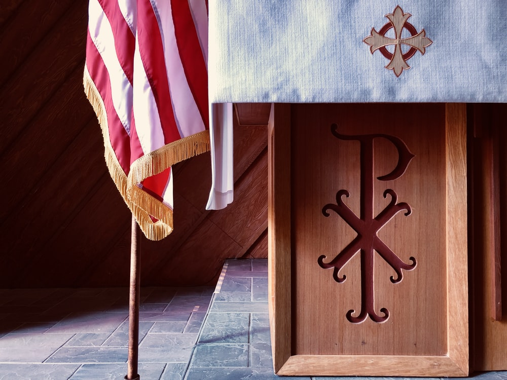 brown wooden cross with flag of us a on top