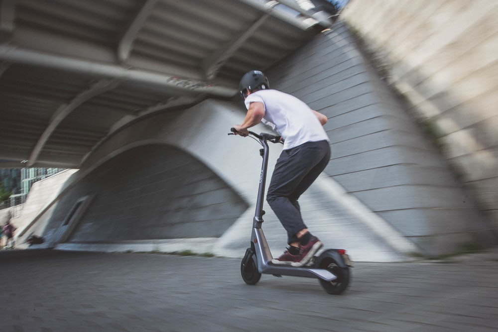 man in white t-shirt riding black and red kick scooter on gray concrete road during