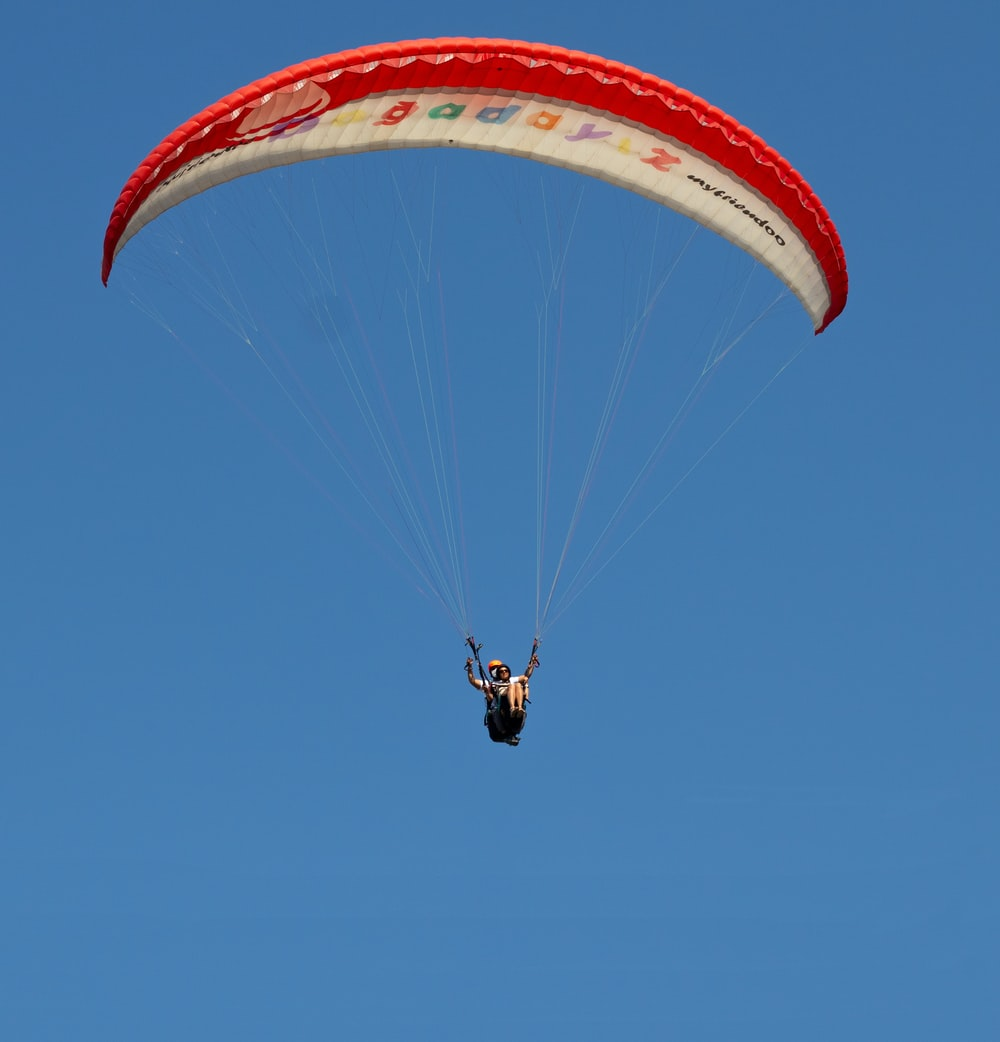 person in yellow parachute in mid air during daytime