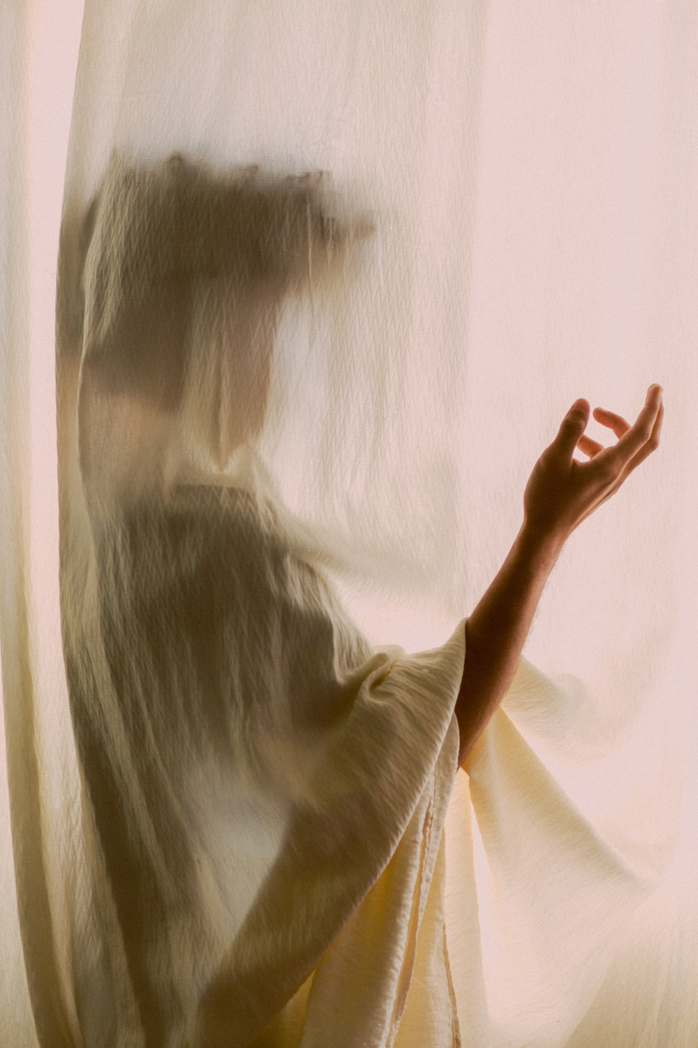 woman in white shirt covering her face