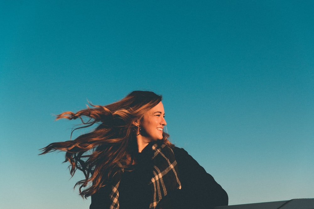 woman in black jacket standing under blue sky during daytime