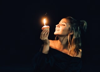 woman in black dress holding lighted candle