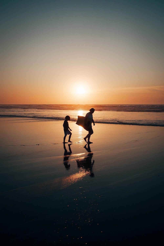 2 men walking on beach during sunset
