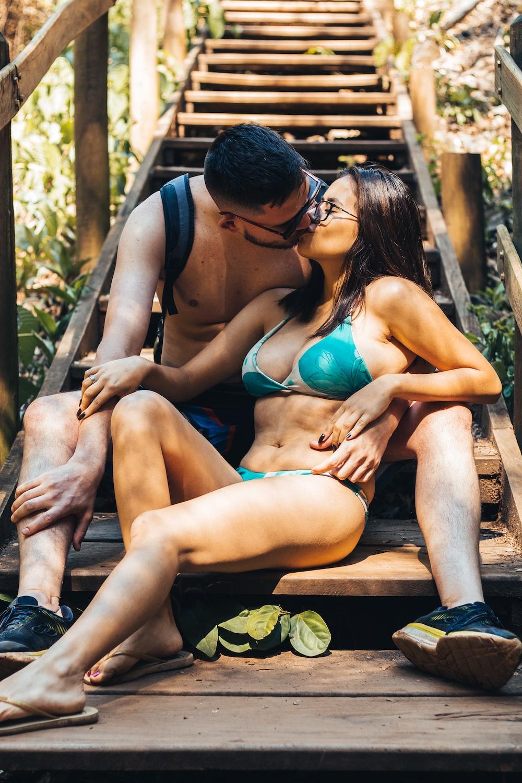 2 women in blue bikini sitting on brown wooden bench during daytime
