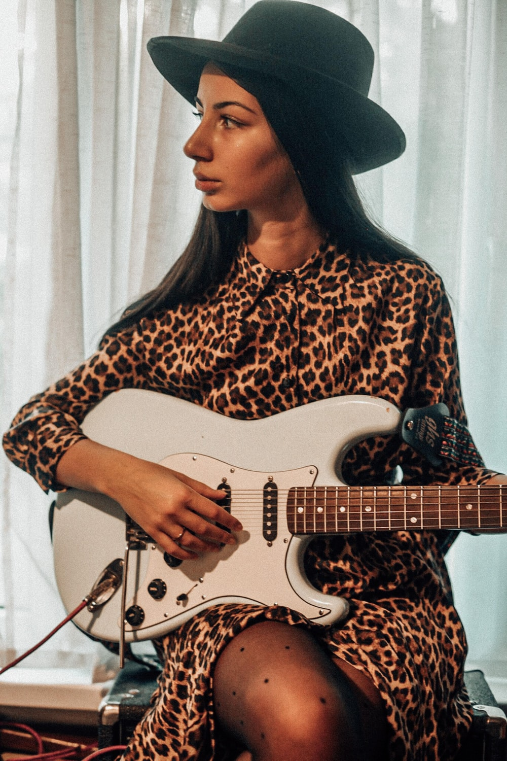 woman in black hat playing white electric guitar